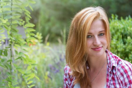 Smiling attractive young woman with slightly disheveled long hair is looking at the camera outdoors.