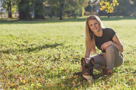 Smiling long haired young girl posing with cute French Bulldog in autumn park looking at the camera.
