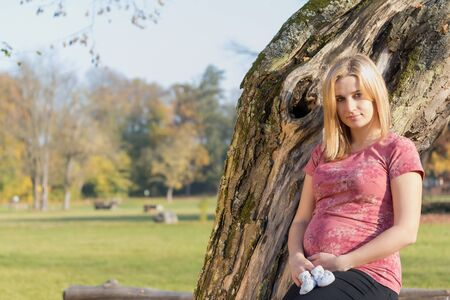 Beautiful young pregnant woman is holding knitted baby booties outdoors. Horizontally. All potential trademarks are removed. Standard-Bild - 134455062
