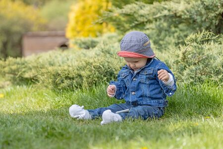 Cute little baby boy sitting outdoors and playing with smart phone. All potential trademarks are removed.