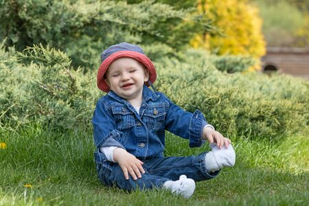 Smiling little baby boy with closed eyes  is sitting in the garden. Standard-Bild