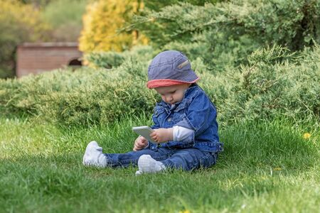 Cute little baby boy is using smart phone sitting on the grass in the garden.