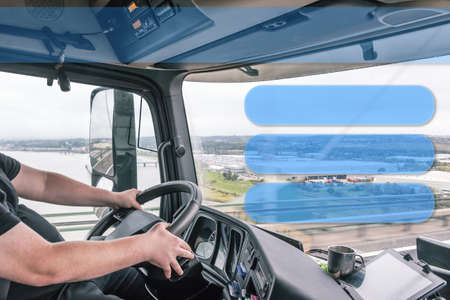 Interior of a truck cab with a driver while driving. Blank rectangles are ready for your use as template, information or presentation. Stock Photo