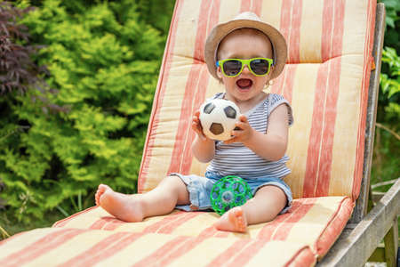 Happy little baby boy with open mouth wearing sunglasses is sitting on the deck chair holding small soccer ball toy.