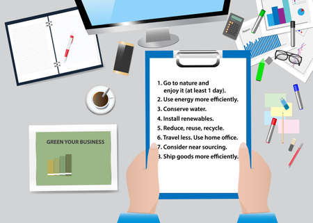Top view of the office desk with office supplies. Hands are holding a paper with steps to green your business presentation. All potential trademarks are removed.