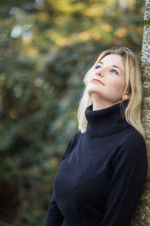 Serious young girl dressed in turtleneck is posing in the autumn park looking up. Vertically.