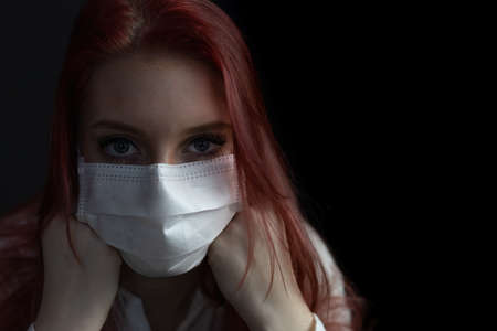 Closeup low key portrait of beautiful redhead young woman with a disposable protective face mask on the black background.