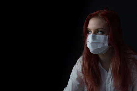 Low key portrait of young redhead woman at home on quarantine with medical mask. Woman is looking at the side. Фото со стока