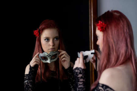Attractive redhead young woman is looking at herself in the mirror holding a carnival mask. Horizontally.