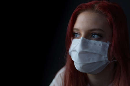 Closeup low key portrait of young redhead woman at home on quarantine with medical mask. Woman is looking at the side. Фото со стока