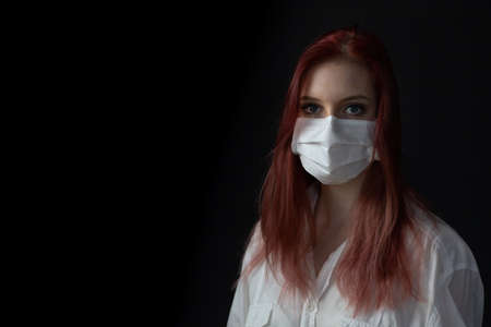 Low key portrait of young redhead woman at home on quarantine with medical mask on black background.