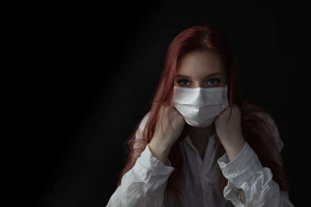 Low key portrait of angry redhead young woman with a medical face mask on the black background. Фото со стока