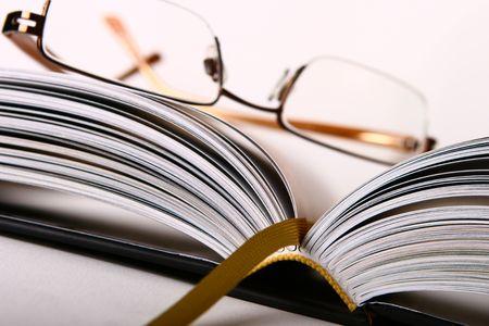 rimmed: Half-rimmed gafas en sesi�n abierta duro-libro con el respaldo tejidas libro favorito y  's en la columna vertebral claramente. Profundidad de campo.
