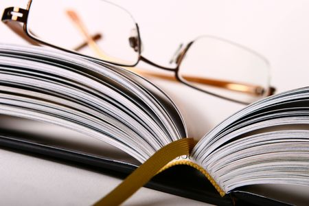 black rimmed: Half-rimmed glasses sitting on open hard-backed book with woven bookmark and books spine in sharp focus. Shallow depth of field.