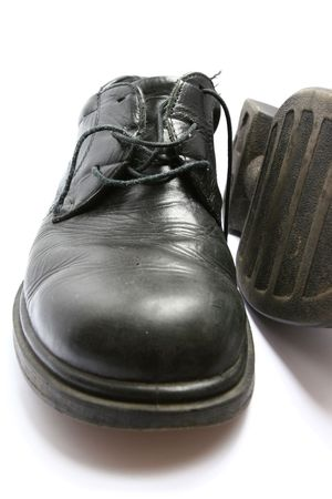 tatty: Well-worn black leather shoes with rubber sole on white background with slight shadow to front. One shoe lying on side.