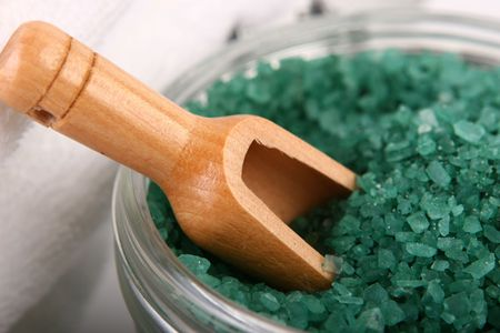 suggests: Close-up of bath salts with wooden scoop and towels in background - suggests pampering and relaxation.