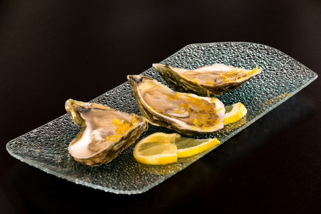 Large oysters on platter with lemon photo
