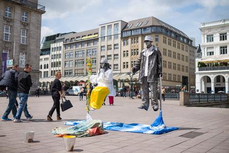 levitacion: Hamburgo, Alemania - 23 de junio 2014: Los artistas callejeros realizan levitaci�n arte visual cercana Rathausmarkt mientras la gente camina pasado sorprendidos