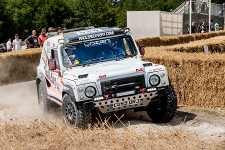 west sussex: Chichester, West Sussex, UK - June 29, 2014: Landrover rally vehicle slides around corner with hay bails separating onlookers from the course  Editorial