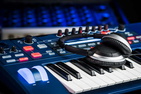 music production: Headphones on top of a synthesizer inside a recording studio
