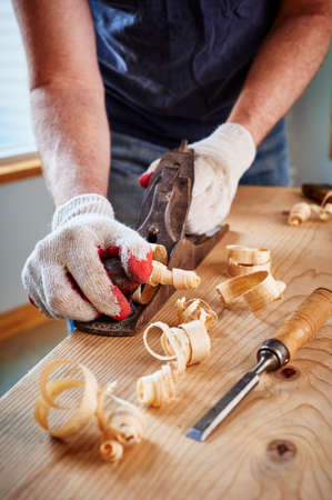 woodwork: a man doing woodwork by using an old plane