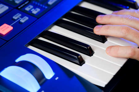 person playing notes on a synthesizer