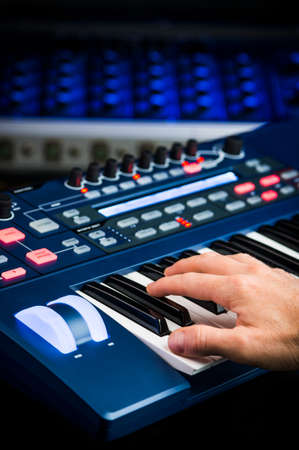 music production: person playing a synthesizer in a recording studio