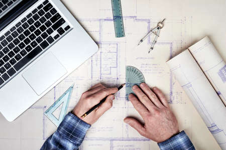 architectural building: Architect working with blueprints