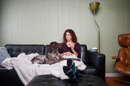 een jonge vrouw die haar hond een traktatie Stockfoto