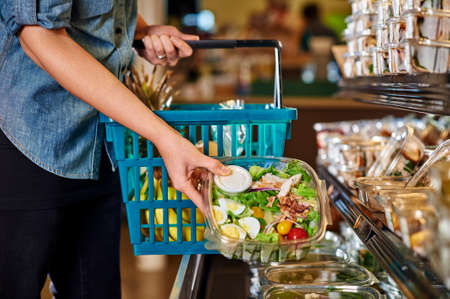 happy shopper: woman buying a salad at a grocery store