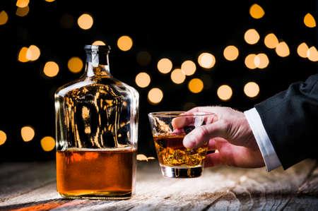 een persoon die een glas whisky
