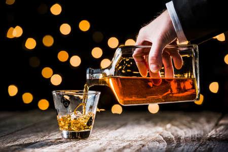 een persoon gieten whiskey in een glas