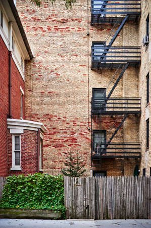 fire escapes on the side of a brownstone apartment building Stock Photo