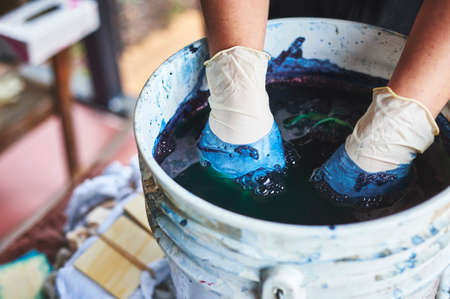 a woman dying fabric with indigo dye. Stock Photo