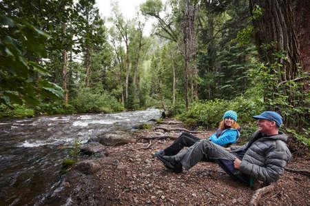 een man een vrouw die naast een bergrivier kampeert Stockfoto