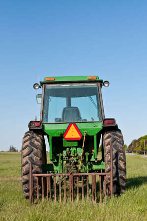 Green Tractor in a Farm Field with Blue Sky photo