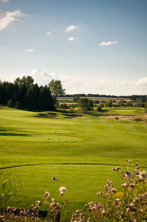 A hole on a golf course with green grass and blue sky. Stock Photo