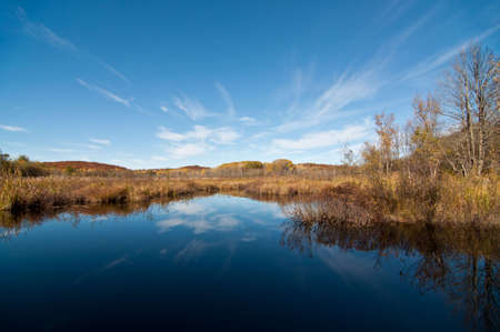 An autumn landscape with a deep blue pond that reflects the clouds and foliage. photo