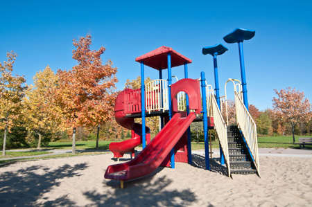 playground equipment: A neighborhood park with brightly colored playground equipment and trees in the fall. Stock Photo