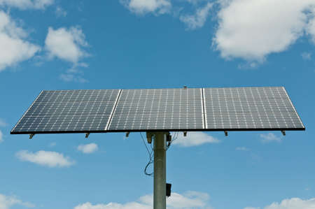 A modern photovoltaic solar panel array generates electricity with blue sky and clouds in the background.