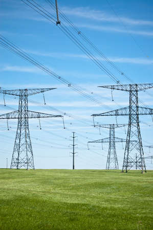 hoogspanningsmasten: Power lijnen die dwars over een groen veld met blauwe lucht op de achtergrond. Stockfoto
