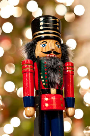 A shiny wooden nutcracker stands in front of an out of focus Christmas tree. Stock Photo