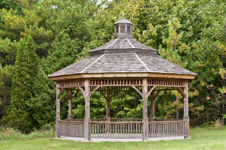 A wooden gazebo stands in front of some green trees in a park.