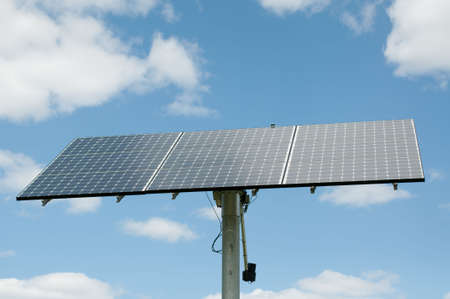 generates: A modern photovoltaic solar panel array generates electricity with blue sky and clouds in the background.