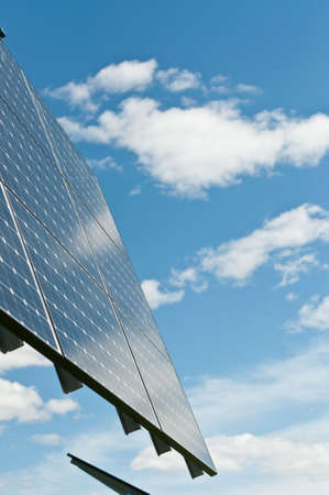 A photovoltaic solar panel array with a blue sky and puffy white clouds in the background. Stock Photo