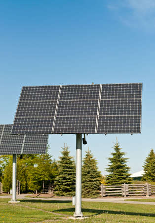 Two arrays of photovoltaic solar panels stand in the grass in a public park. photo