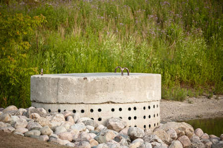 perforated: Part of a pond based stormwater management system to prevent flooding in a suburban area. Stock Photo
