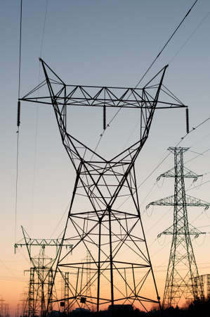 electrical wires: A long line of electrical transmission towers carrying high voltage lines. Stock Photo