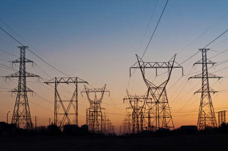 A long line of electrical transmission towers carrying high voltage lines. Stock Photo