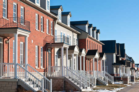A row of recently built townhouses on a suburban street in winter.